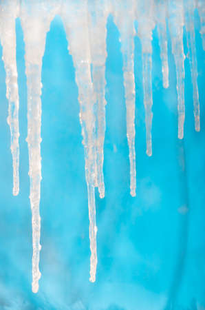 Frozen icicles hang on a clear day on a blue background