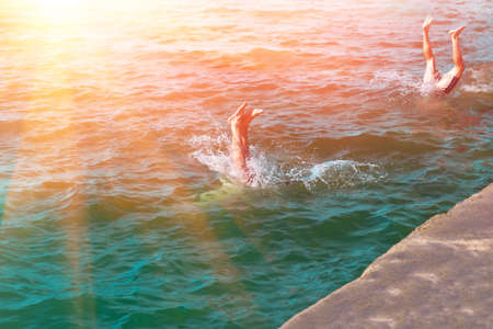 he: A young mans legs disappearing as he dives into the in a refreshing sea, ocean, On a hot summer day Stock Photo