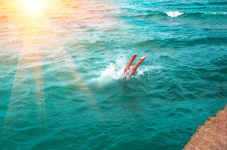 A young mans legs disappearing as he dives into the in a refreshing sea, ocean, On a hot summer day Stock Photo
