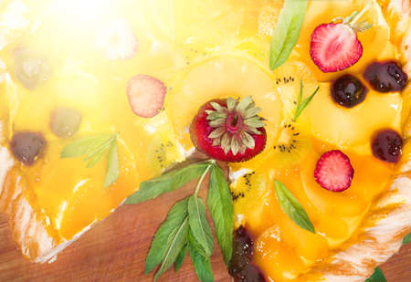 grass cutting: Fruit pizza with strawberries, cherries, cream, jelly, pineapple, kiwi and mint leaves, lying on a wooden cutting board, home-made. dessert background, closeup