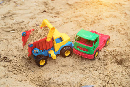 childrens toys trucks on the sand imitate a traffic accident, an accident in sandbox after a rain in the autumn, Stock Photo