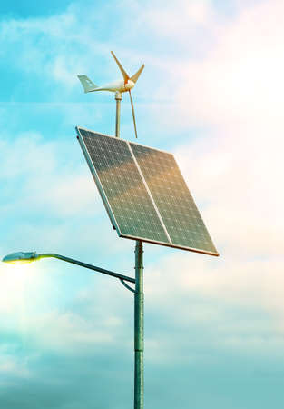 Solar panel and wind turbine under cloudy blue sky on the background of the building