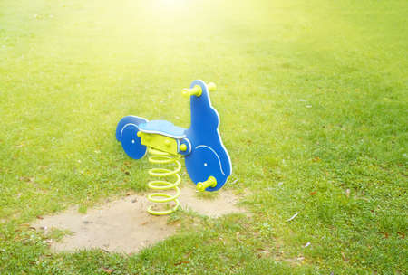 blue motorcycle on the green grassy lawn, childs swing on a steel spring Stock Photo