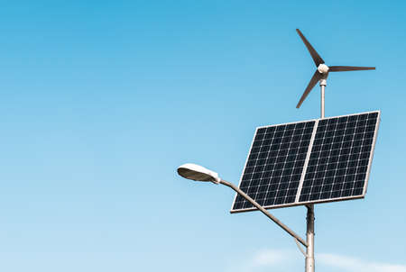 Solar panel and wind turbine under blue sky