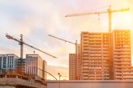 Construction of modern altitudinal buildings of concrete and glass early in the morning during sunrise Banco de Imagens