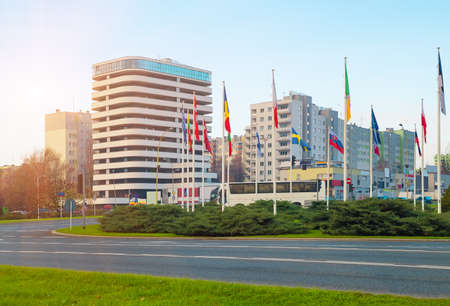 Flags countries near roadway against backdrop large modern business office building 스톡 콘텐츠