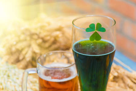 Mug of light beer and green Irish beer close-up in Patricks Day. Beer in a glass closeup