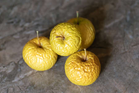 Wrinkled yellow old apples lies on the table top, closeup on neutral background.