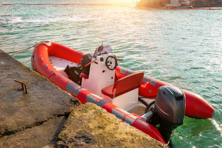 Red rescue inflatable boat moored to the sea pier, closeup. Empty marine rescue boat.