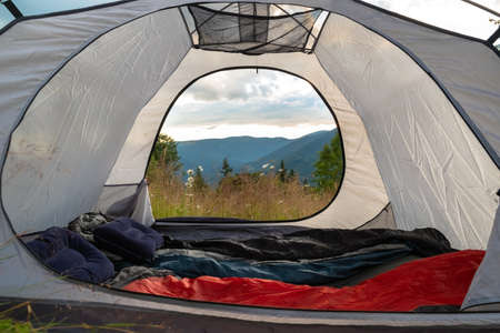 View from the tourist tent on the mountains, meadow, herbs, flowers, early in the morning when the sun rises. Camping equipment including a sleeping bag and pillow. Tourist tent.Turistic background