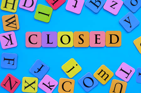 The word closed spelled in multi colored letters and blue background. Concept of closed schools and daycare centers