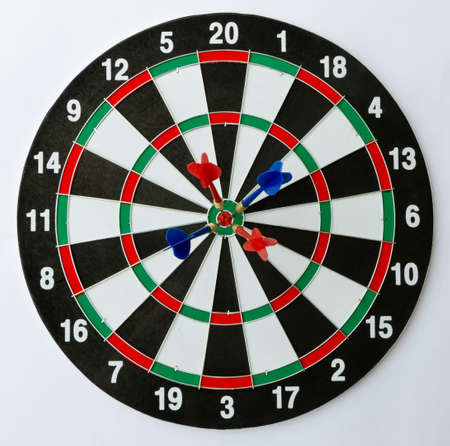 Dartboard with four darts on the bulls eye.