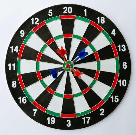 dartboard: Dartboard with four darts on the bulls eye.