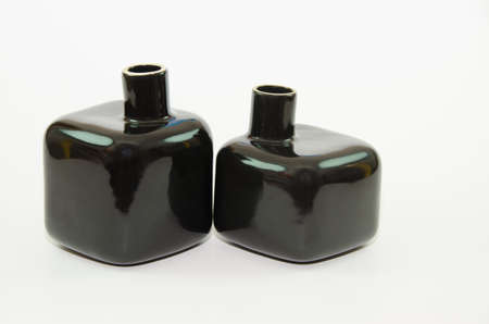 a jar stand: Two black bottles on a white background.