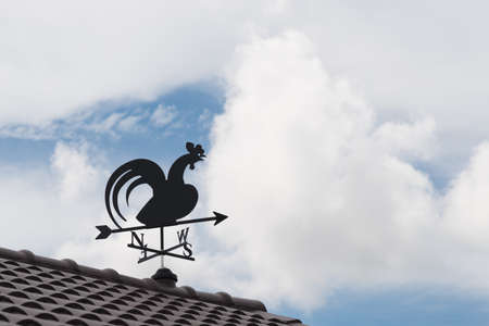 north arrow: Weathervane with cock above an arrow and the four cardinal points North East West South Stock Photo