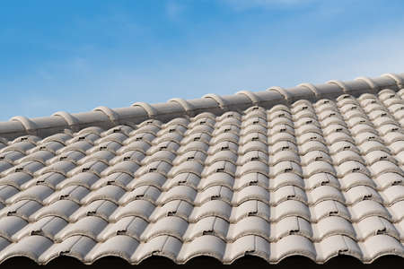 Rows of roof tiles on the top of house with sky background. Stock Photo