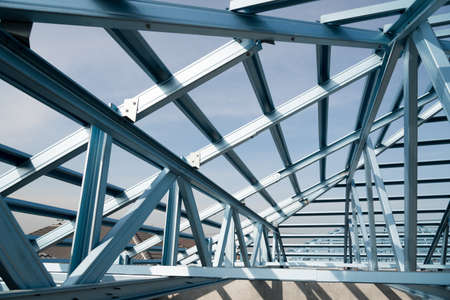 prefabricated buildings: Structure of steel roof frame for building construction on sky background.
