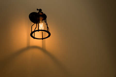 Wall lamp with yellow shade on cement wall. Stock Photo