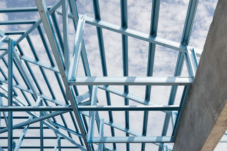 rafter: Structure of steel roof frame for building construction on sky background.