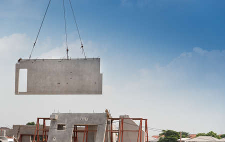 Construction site crane is lifting a precast concrete wall panel to installation building. Stockfoto