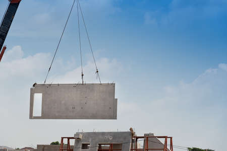 Construction site crane is lifting a precast concrete wall panel to installation building. Imagens
