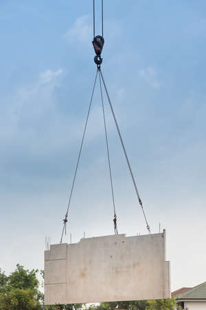 Construction site crane is lifting a precast concrete wall panel to installation building. Stock Photo