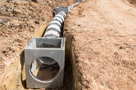 Concrete drainage pipe and manhole on construction site.