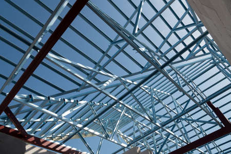Structure of steel roof frame for building construction isolated on blue sky background. Archivio Fotografico