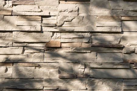 Pattern of decorative brown and yellow slate stone wall surface with wood shadows leading down.