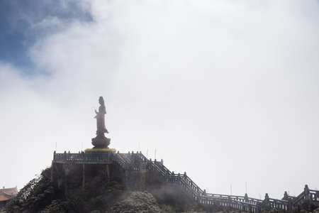 Guan Yin statue standing in the midst of the fog.