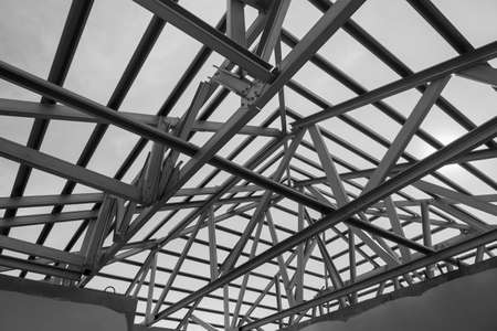 Structure of steel roof frame for building construction. Black and white photo.