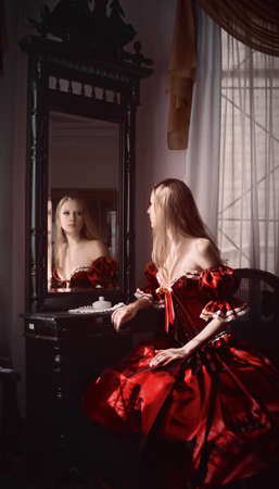 girl in red dress: Woman and mirror Stock Photo