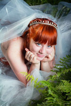 Redhead bride lying on the green grass photo