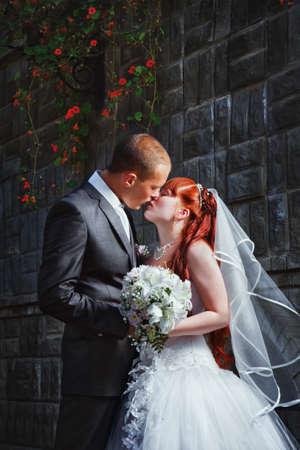Kleurrijke bruiloft schot van bruid en bruidegom kussen Stockfoto