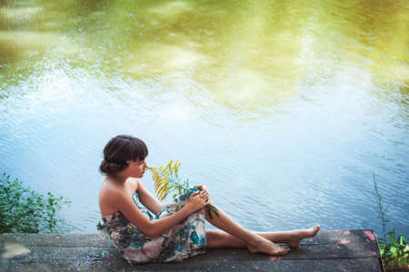wood nymph: Girl sitting by a lake
