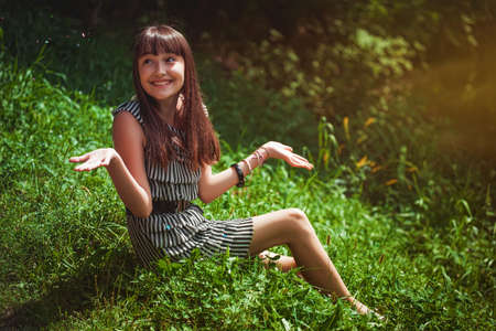 wood nymph: Girl sitting on a grass Stock Photo