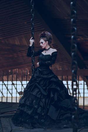 vestidos antiguos: Misteriosa mujer vestida de gótica vestido posando en el edificio arruinado