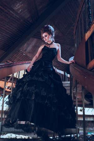 Mysterieuze vrouw gekleed in gothic jurk poseren in een vervallen gebouw