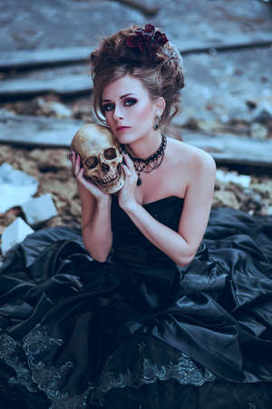 Mysterious woman dressed in gothic dress posing in ruined building photo