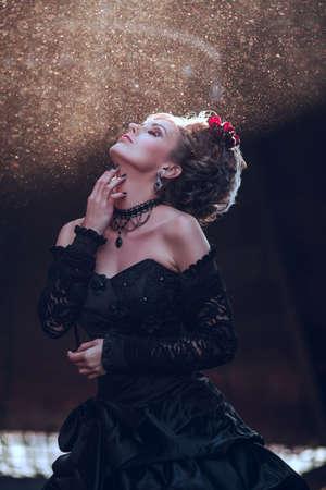 Mysterieuze vrouw gekleed in gothic jurk poseren in de verwoeste gebouw Stockfoto