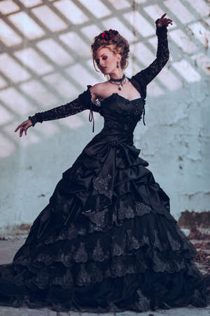 aristocrat: Mysterious woman dressed in gothic dress posing in ruined building