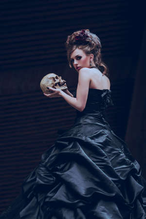 Mysterious woman dressed in gothic dress posing in ruined building