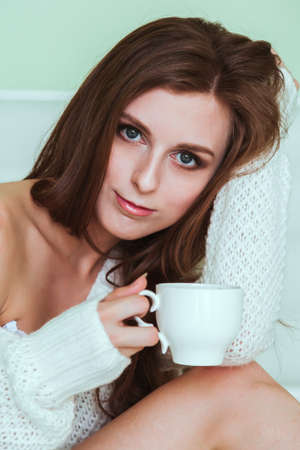 Soft portrait of young woman sitting on the bed with a cup of coffee photo