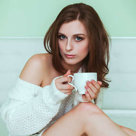 Soft portrait of young woman sitting on the bed at home with a cup of coffee photo