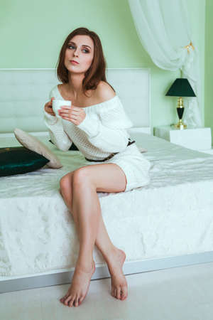 woman sweater: Soft portrait of young woman sitting on the bed at home Stock Photo