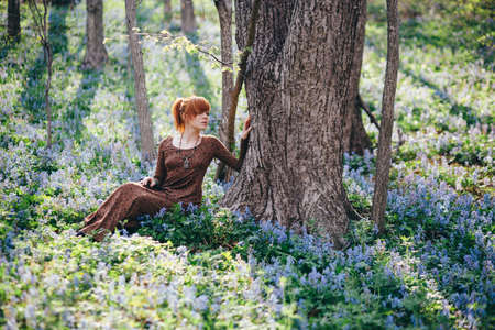 outsides: Beautiful young woman in the forest with spring flowers Stock Photo