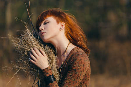 redhaired: Young redhead woman walking in golden dried grass field