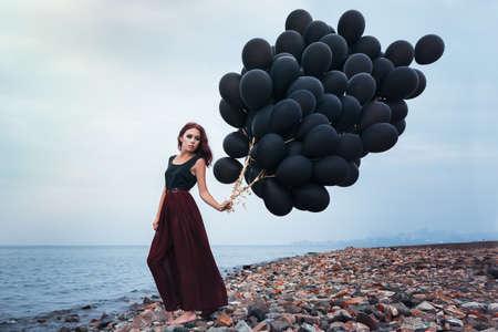 Beautiful girl walking with black balloons photo