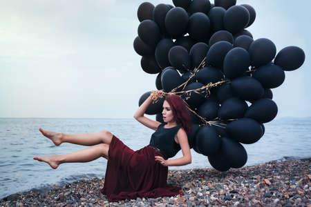 levitate: Beautiful girl walking with black balloons