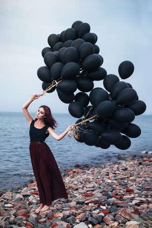 helium balloon: Beautiful girl walking with black balloons